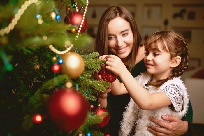 Madre e hija decorando el árbol de Navidad