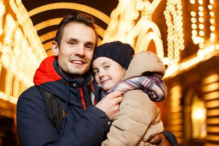 Padre e hija abrazados en una calle iluminada en Navidad